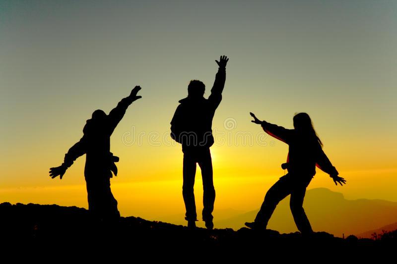 Happy men silhouette at sunrise. A group Happy men silhouette at sunrise royalty free stock photography