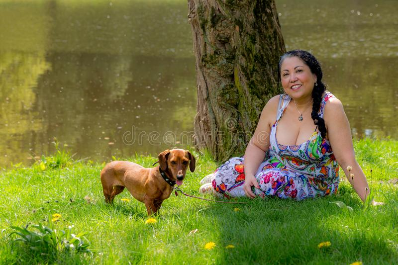 Happy Mexican woman sitting on the grass with her dachshund by a lake royalty free stock image