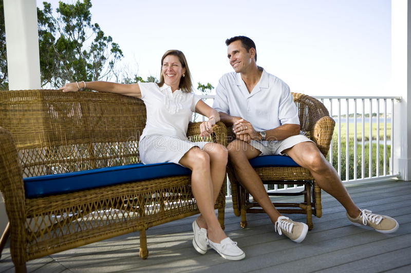 Happy mid-adult couple sitting together on terrace. On vacation stock photo