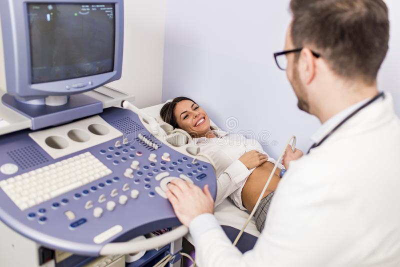 Happy mid adult female patient going through abdomen ultrasound. At clinic stock photography