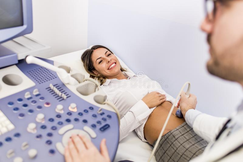 Happy mid adult female patient going through abdomen ultrasound. At clinic royalty free stock images
