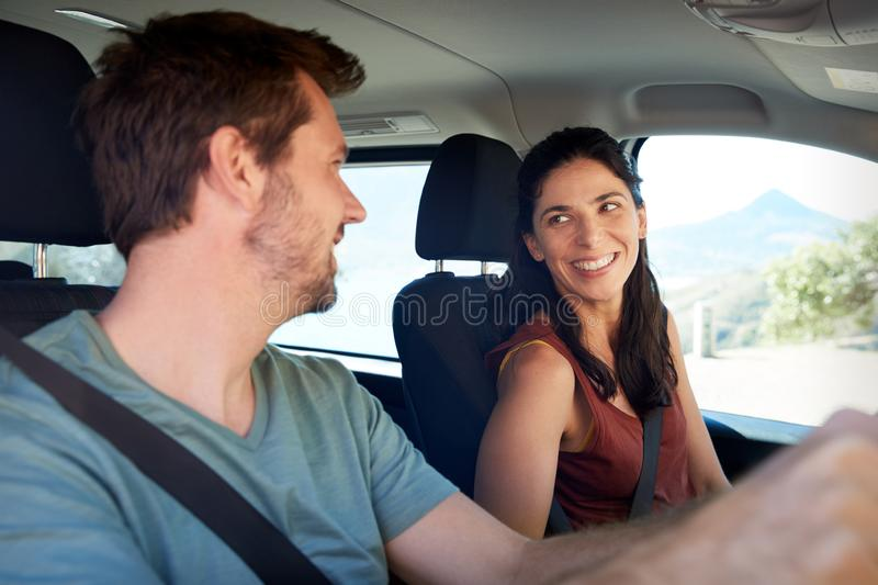 Happy mid adult white couple driving in their car, smiling at each other, close up, side view stock photos