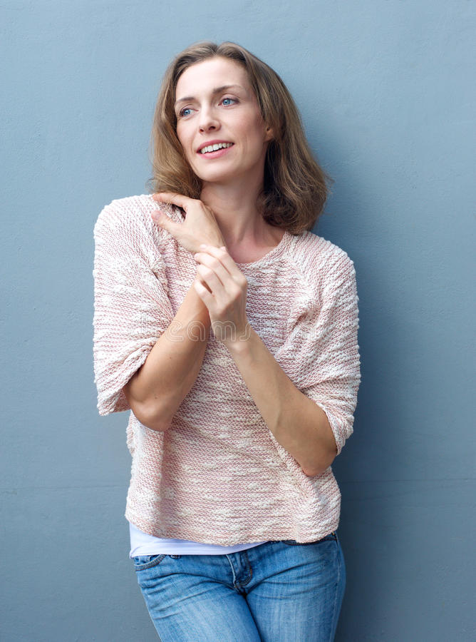 Happy mid adult woman in jeans and sweater stock images
