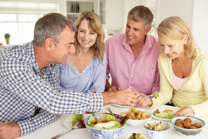 Happy Mid age couples enjoying meal at home stock image