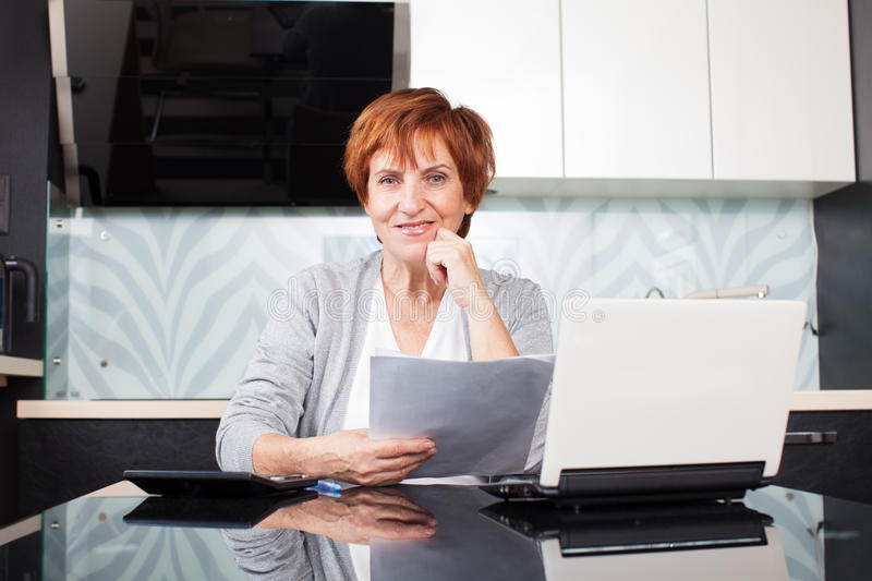 Happy mid businesswoman. Happy businesswoman with documentation at home royalty free stock images