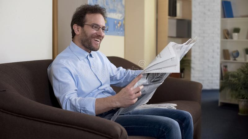 Happy mid-forties male reading newspaper, relaxed person sitting on sofa, press royalty free stock photos
