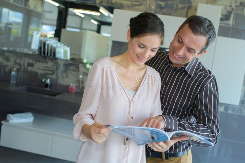Happy middle-age couple with brochure at store stock photo