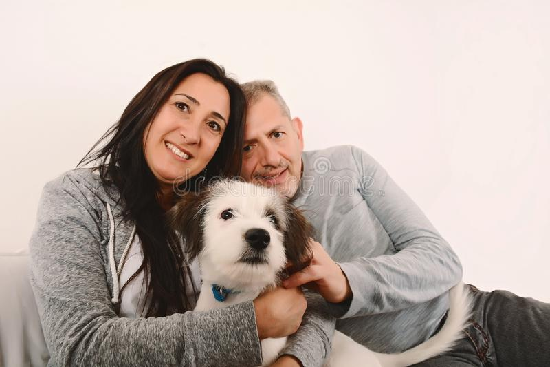 Happy middle-age couple with puppy dog. Indoors stock images