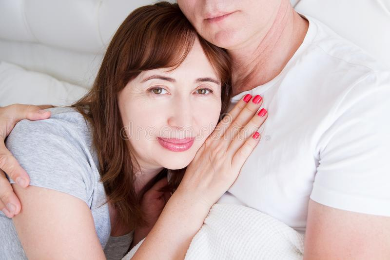 Happy middle age family couple in bed. White interior. Love and healthy relationships. Husband and wife portrait.  stock images