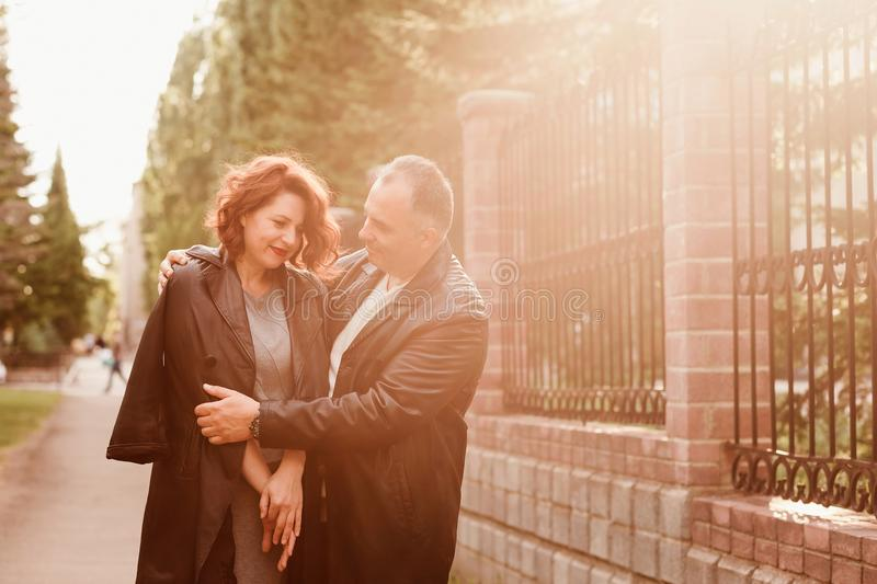 Happy middle-age man and woman hugging outdoors, Sunset backlight in summer royalty free stock images