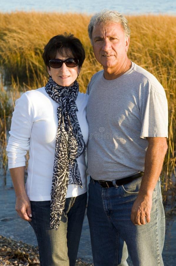 Happy middle age senior couple on beach royalty free stock photos