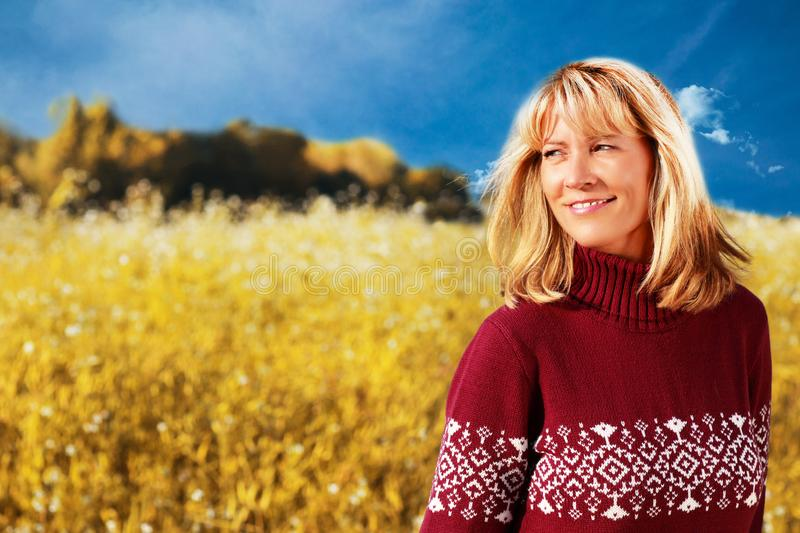 Happy middle age woman in front of a flower field. On a sunny day stock photos