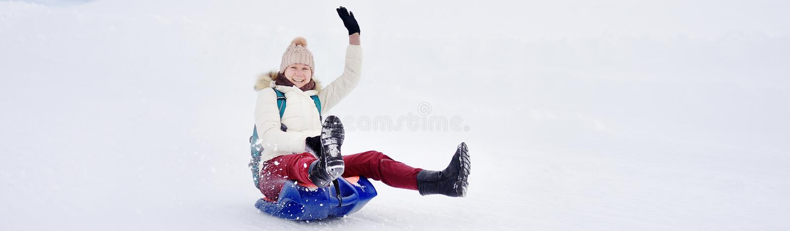 Happy middle age woman having fun during rolling down the mountain slope on sled in Alps. Winter sports with snow. Sledding - typical fun in the Alps mountains stock photo