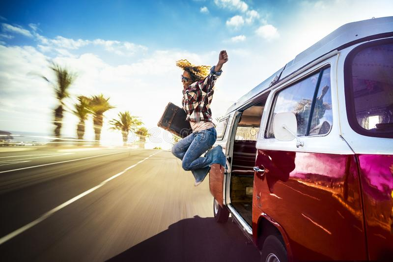Happy middle age woman jumping outside a red vintage van while traveling fast on the road for the joy to start the vacation or. Adventure - wanderlust lifestyle royalty free stock images