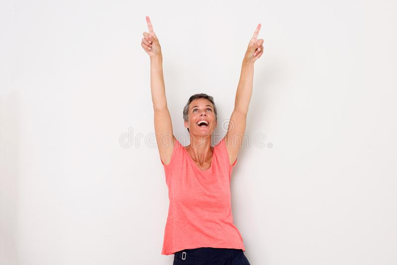 Happy middle age woman laughing with arms raised and pointing fingers up. Portrait of happy middle age woman laughing with arms raised and pointing fingers up stock photos