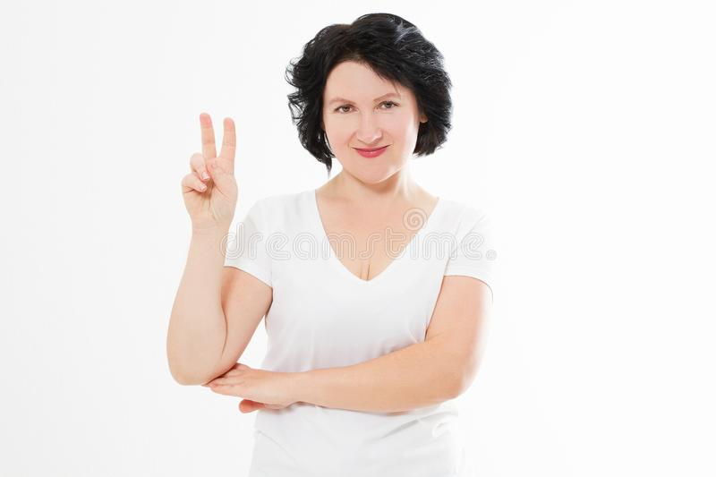 Happy middle age woman showing victory sign isolated on white background. Copy space. Template and blank summer t shirt.  stock image