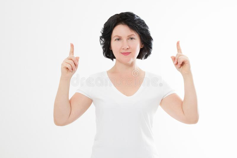 Happy middle age woman in summer blank template t shirt isolated on white background showing copy space by fingers. Mock up.  stock photos