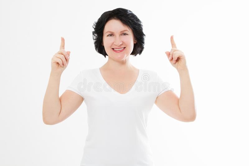Happy middle age woman in summer blank template t shirt isolated on white background showing copy space by fingers. Mock up.  royalty free stock image