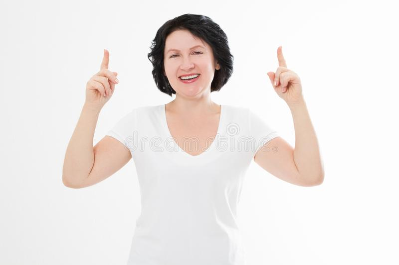 Happy middle age woman in summer blank template t shirt isolated on white background showing copy space by fingers. Mock up.  royalty free stock images