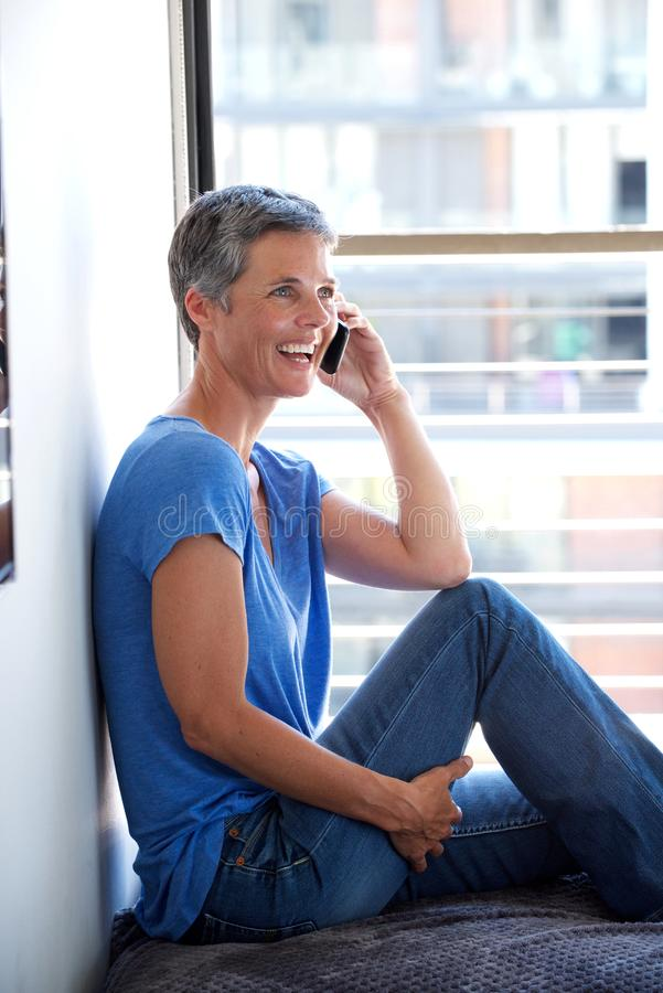 Happy middle age woman talking on mobile phone by window. E portrait of happy middle age woman talking on mobile phone by window stock photo