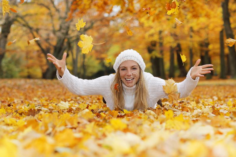 Happy middle age woman throwing yellow autumn leaves. While lying on theground royalty free stock photo