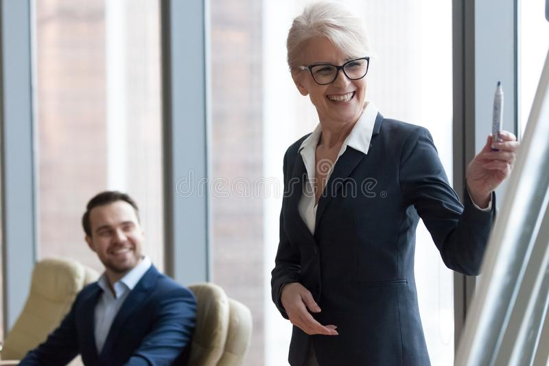 Happy middle-aged businesswoman coach mentor in suit drawing presentation. Happy middle aged businesswoman coach mentor in suit drawing presentation on flipchart royalty free stock images