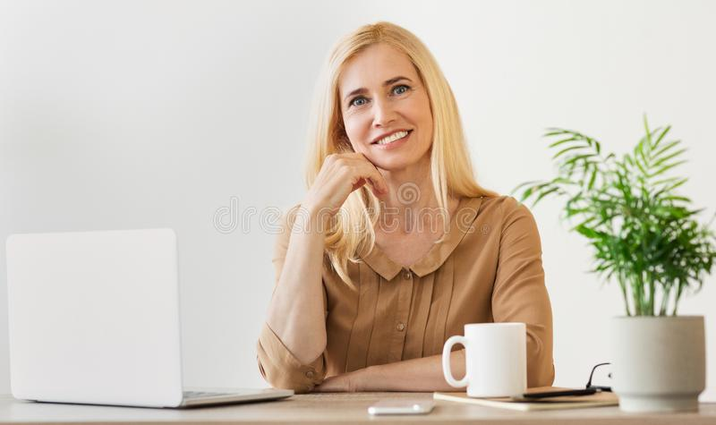 Happy middle-aged businesswoman working in office, smiling to camera royalty free stock photo