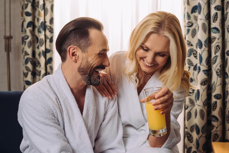 happy middle aged couple in bathrobes drinking juice during breakfast stock photos