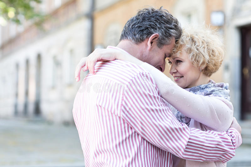 Happy middle-aged couple embracing in city stock photos