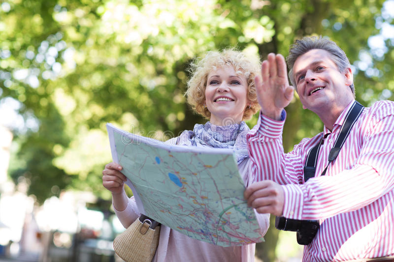 Happy middle-aged couple holding map in city stock images