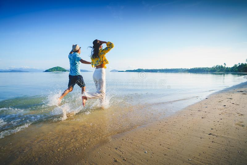 Happy middle aged couple running on a beach royalty free stock photography