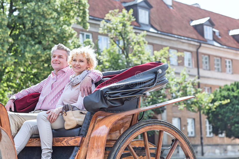 Happy middle-aged couple sitting in horse cart on city street royalty free stock photo