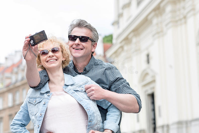 Happy middle-aged couple in sunglasses taking self portrait outdoors stock photo
