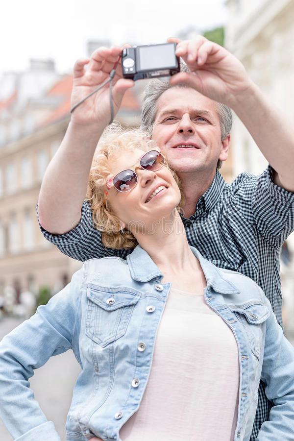 Happy middle-aged couple taking self portrait outdoors royalty free stock photo