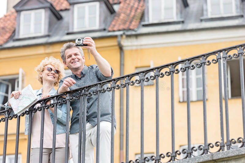 Happy middle-aged couple taking selfie through digital camera against building stock photo