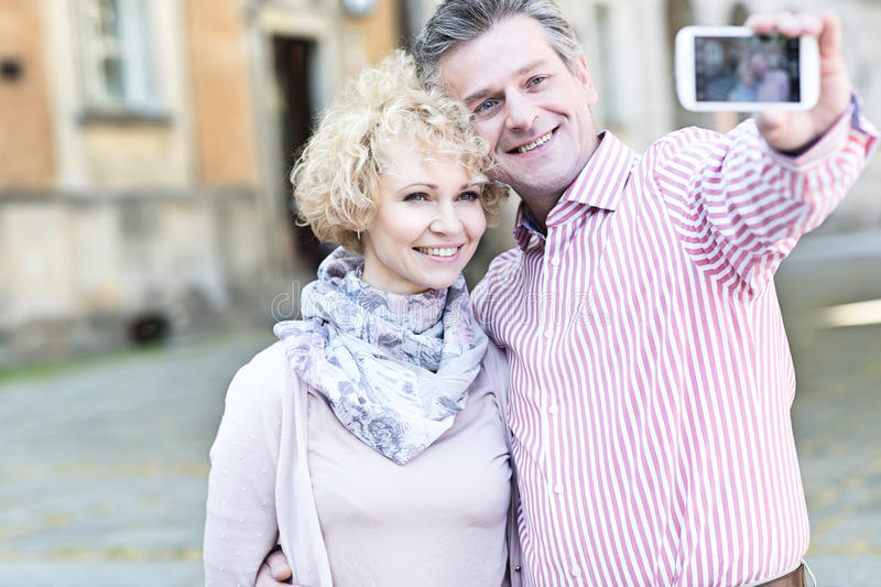 Happy middle-aged couple taking selfie through smart phone in city stock photos