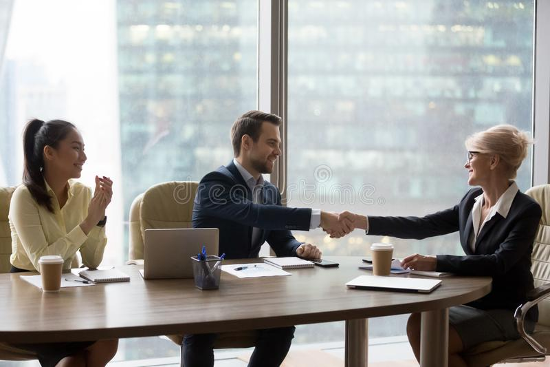 Happy middle-aged executive handshaking new male partner at team meeting. Happy middle aged executive businesswoman handshaking new male partner at diverse team stock photography