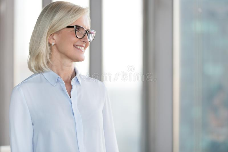 Happy mature female employee dream of future career opportunities royalty free stock image