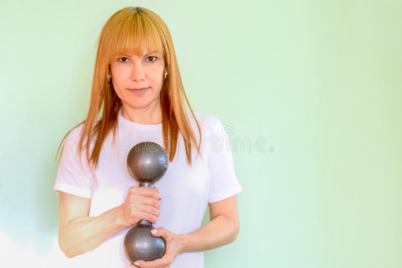 Happy middle aged fitness woman lifting dumbbells smiling and energetic on mint green background. royalty free stock photo