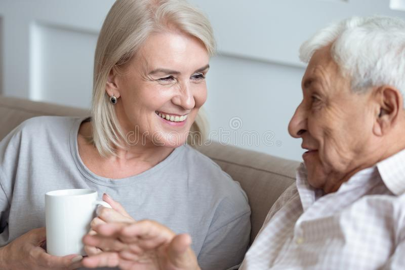 Happy middle aged grey haired woman talking with senior husband. stock image
