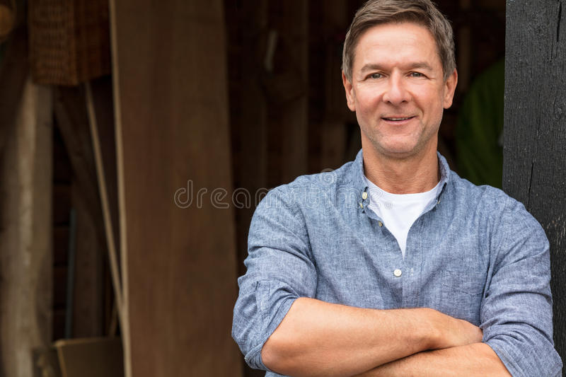 Happy Middle Aged Man Arms Folded by His Garage stock image