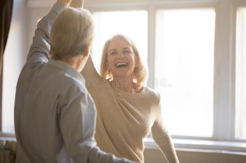 Happy middle aged mature woman enjoying dancing with elder husband royalty free stock photography