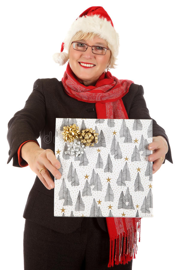Happy middle aged santa woman, gift. Happy Caucasian middle aged woman wearing Santa hat showing Christmas gift . Studio shot. White background stock photography