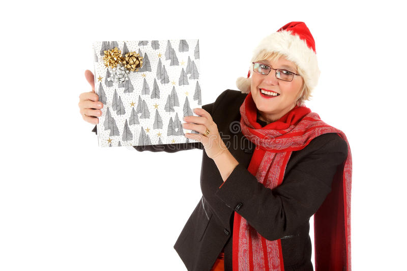 Happy middle aged santa woman, gift. Caucasian middle aged woman wearing Santa hat showing the Christmas gift. Studio shot. White background royalty free stock photo