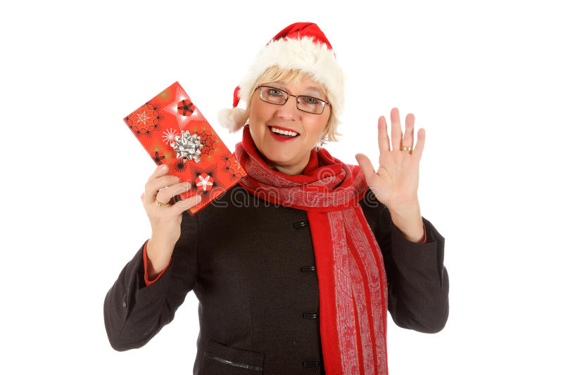 Happy middle aged santa woman, gift. Happy Caucasian middle aged woman with a hand up, wearing Santa hat and showing Christmas gift . Studio shot. White stock photos