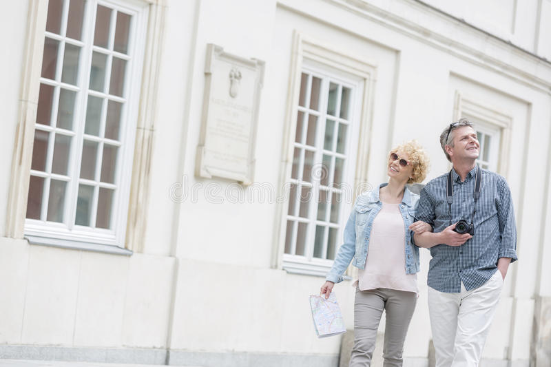 Happy middle-aged tourist couple walking arm in arm by building stock photography