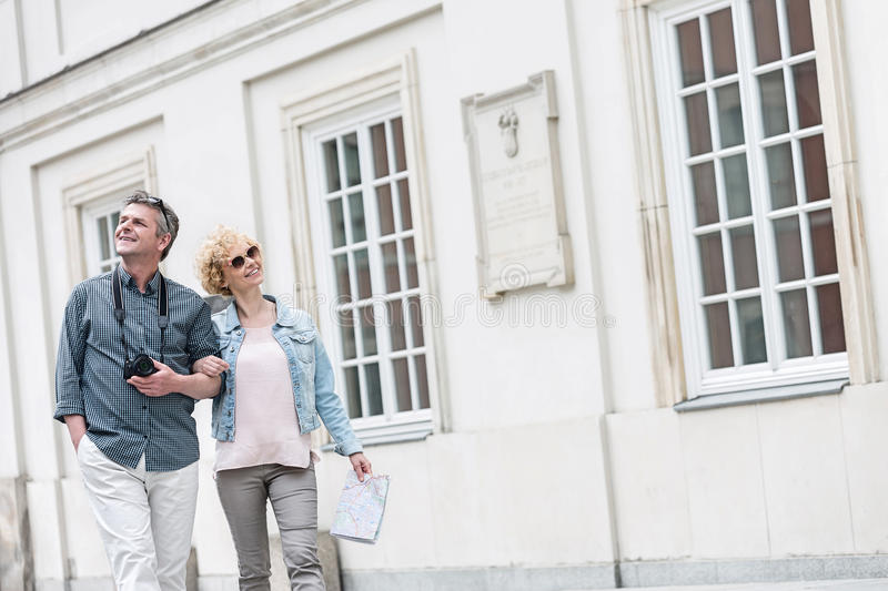 Happy middle-aged tourist couple walking arm in arm by building stock images