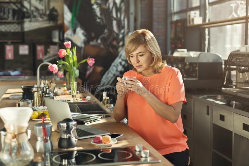 Happy middle-aged woman barista working on laptop. Happy middle-aged woman barista or manager working on laptop, making an order online and drinking coffee at stock images
