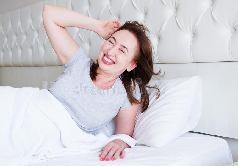 Happy middle aged woman lie in bed. Good morning and sleep concept. Menopause and healthy lifestyle. Selective focus.  royalty free stock photography