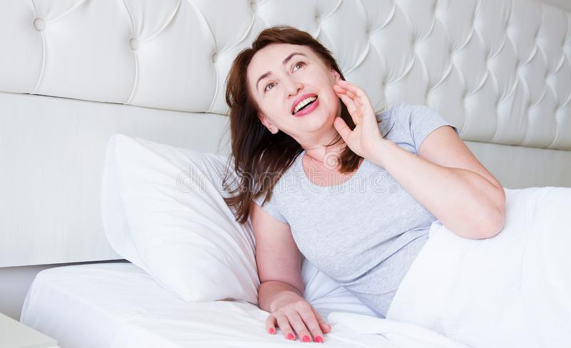Happy middle aged woman lie in bed. Good morning and sleep concept. Menopause and healthy lifestyle. Selective focus. Banner.  royalty free stock photos